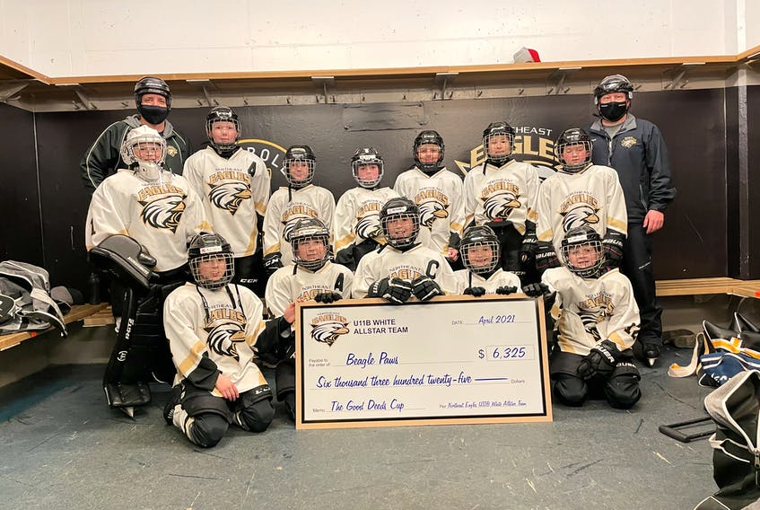 The U11 Northeast Eagles white all-star team posing in front of their cheque of $6,325 for the charity Beagle Paws.