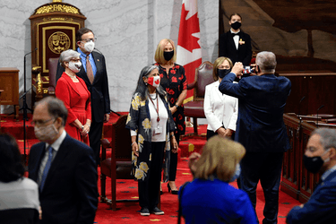 Senators take a photo as they arrive for the opening session in the Senate chamber in Ottawa on Sept. 23, 2020.