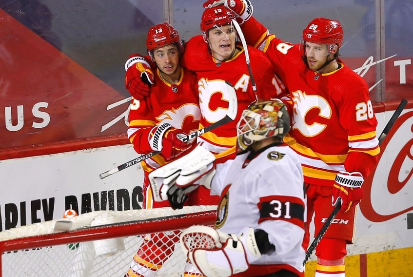 Johnny Gaudreau and his Calgary Flames teammate celebrate Gaudreau's first-period goal against Ottawa Senators goalie Anton Forsberg on May 9, 2021.