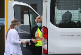 Nurses prepare a patient for their vaccine, as they sit in their vehicle at the drive-thru vaccination site near Dartmouth General Hospital Monday May 10, 2021. The patient's vehicle was too tall to fit in the drive-thru garage so the nurses took the vaccine to his vehicle.
