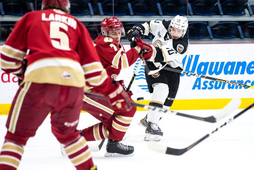 Charlottetown Islanders captain Brett Budgell, right, fires a shot towards the Acadie-Bathurst Titan goal during Game 3 of the Quebec Major Junior Hockey League's Maritimes Division final Tuesday in Shawinigan, Que.