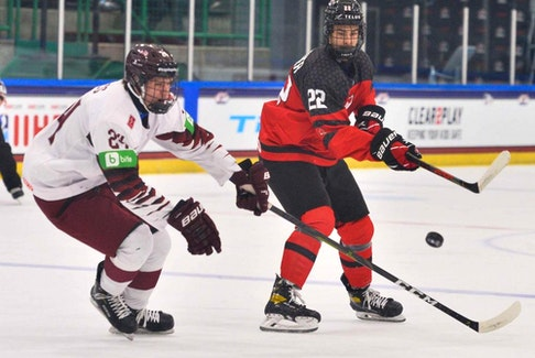 Canada's Dylan Guenther (No. 22) makes a pass in front of Martins Sulcs (No. 24) of Latvia in a group game at the IIHF U-18 world championships in Frisco, Texas, on April 28, 2021.