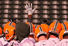 A lone hand is raised during a team huddle during training camp for the Edmonton Football Club at Commonwealth Stadium on May 20, 2019.
