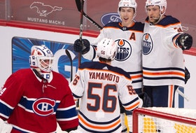 Edmonton Oilers forward Ryan Nugent-Hopkins (93) celebrates his goal with teammates Leon Draisaitl (29) and Kailer Yamamoto (56) after scoring the second goal on Montreal Canadiens goaltender Jake Allen (34) during first period NHL hockey action in Montreal, Monday, May 10, 2021.