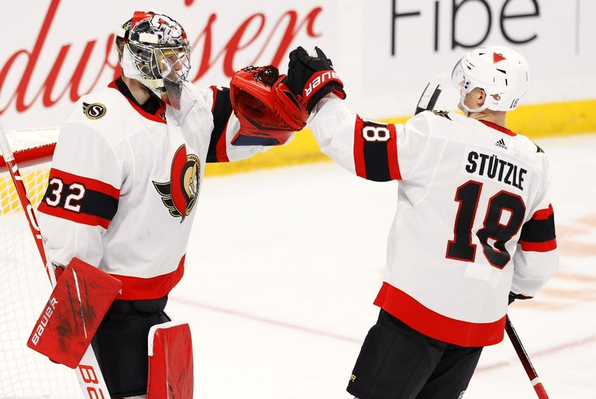 Ottawa Senators goaltender Filip Gustafsson (32) and left wing Tim Stuetzle (18) celebrate their win against the Winnipeg Jets at Bell MTS Place on May 9, 2021 .