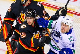 Calgary Flames defenceman Noah Hanifin battles against Tanner Pearson of the Vancouver Canucks during a game earlier this season.