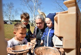 Albany Cluney, 4, left, Ronin Mooney, 2, Nolan Shaw, 2, and owner/director Jamie Mosher spend a sunny afternoon making mud cakes in the outdoor kitchen at Rainbow Beginnings Early Learning Centre Inc. in St. Theresa on May 11.