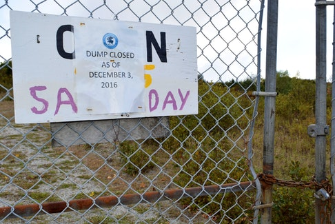 A paper sign announcing the Town of Shelburne dump was closed as of Dec. 3, 2016 is stapled over a wooden sign on the gate that says the site is open on Saturdays  in this 2018 photo. The paper sign recently met its demise due to do wear and tear from the weather, causing concern for the Shelburne based South End Environmental Injustice Society (SEED) that people may think the site was actually operational. In an email to the group, Mayor Harold Locke assured them it would be replaced. KATHY JOHNSON