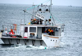 One crewman stands at the ready with a gaff to grab the approaching buoy line in the water while the other tends to the catch  aboard the fishing vessel Another Expense while fishing lobster along the Woods Harbour coastline. The six-month commercial lobster  fishery is southwestern Nova Scotia and the South Shore closes on May 31. KATHY JOHNSON