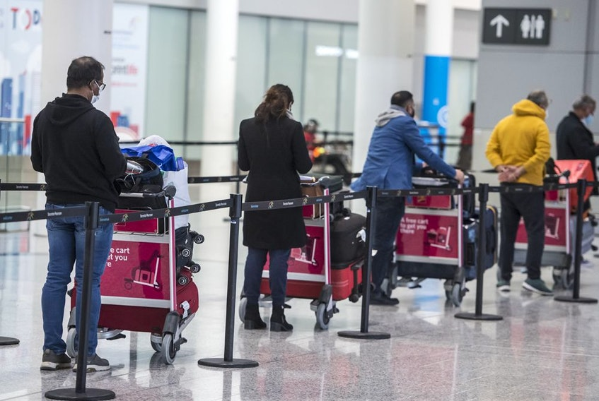 Travellers await transportation to a quarantine hotel after arriving at Pearson International Airport on Feb. 24, 2021.