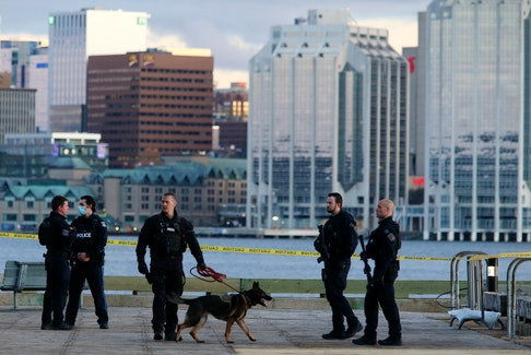 """FOR NEWS STORY: Halifax regional police confer as they secure the area following a shooting at Alderney Landing in Dartmouth Wednesday evening May 12, 2021. Police responded to a report of gun shots and located an adult male with life-threatening injuries """"consistent with a gunshot wound. """"  Officers took three adults into custody not far from the area.....ALL THE DETAILS AT THIS TIME.  TIM KROCHAK PHOTO"""