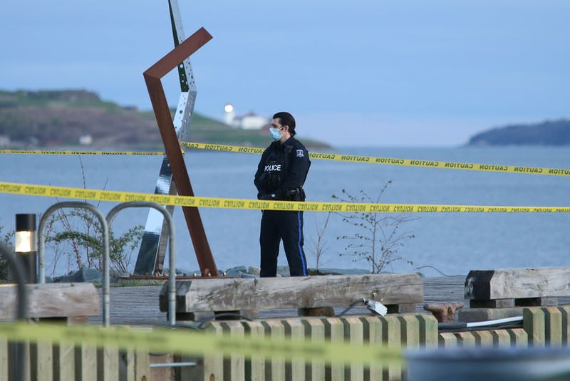 A police officer guards the crime scene at Alderney Landing in Dartmouth on Wednesday evening.