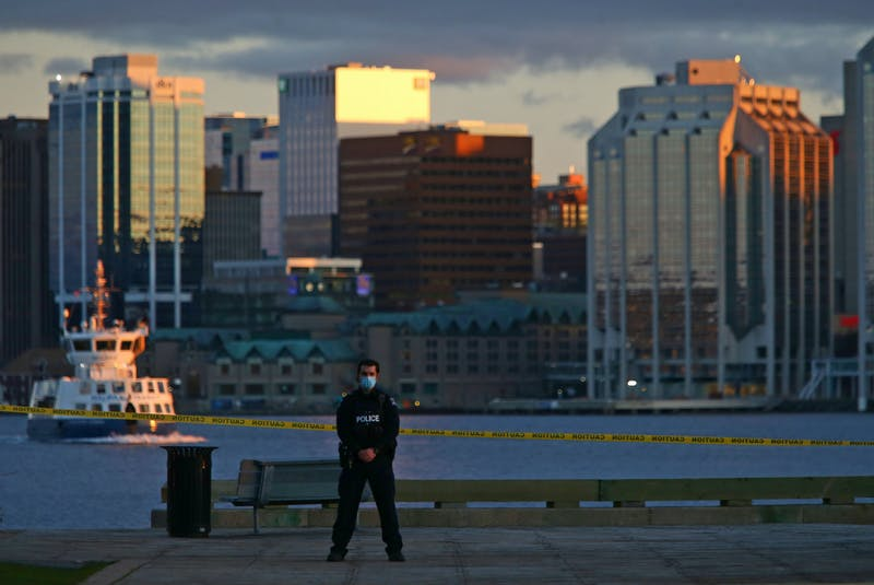 An officer guards the shooting scene as a Halifax Transit ferry crosses the harbour near sunset Wednesday evening. - Tim Krochak