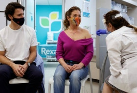 Canada's Prime Minister Justin Trudeau watches as his wife Sophie Gregoire is inoculated with AstraZeneca's vaccine in Ottawa  on April 23, 2021.