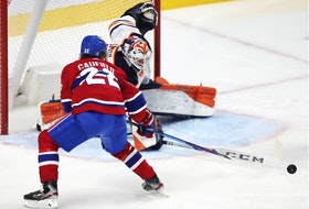Cole Caufield has the puck poked away from him by Edmonton Oilers goalie Mike Smith during the third period in Montreal Wednesday May 12, 2021.
