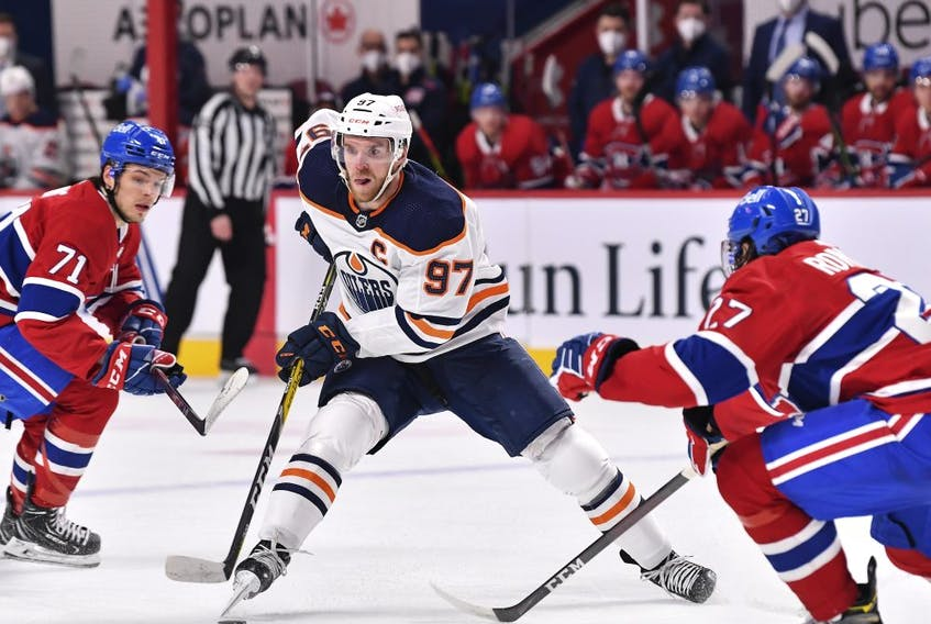 Connor McDavid (97) of the Edmonton Oilers skates the puck past Jake Evans (71) and Alexander Romanov (27) of the Montreal Canadiens during the first period at the Bell Centre on May 12, 2021 in Montreal.