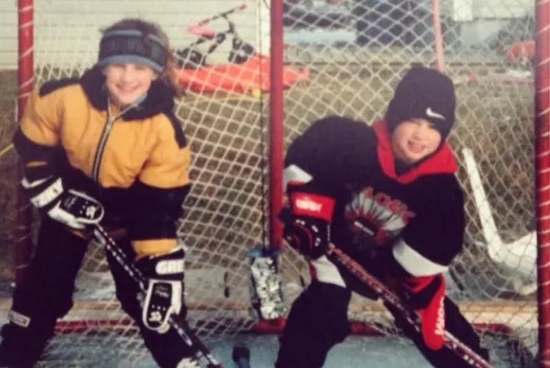 Brennan Saulnier, right, poses with older sister Jill in their backyard rink. - Contributed