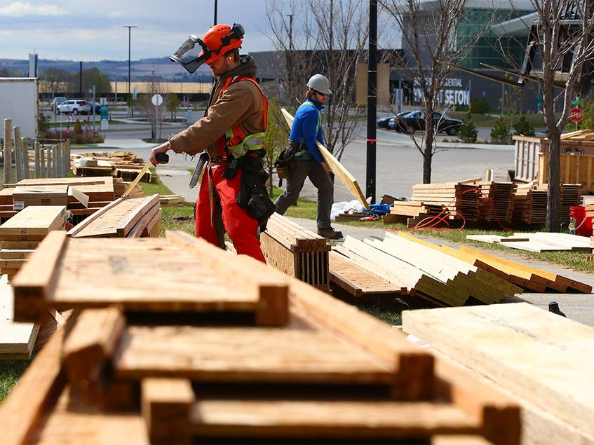 Construction workers organize lumber at a condominium development in Seton on Tuesday, May 11, 2021. Surging lumber prices have created a spike in lumber thefts in Calgary. - Gavin  Young/Postmedia