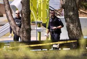Halifax police officers walk past playground equipment near the scene of a fatal shooting at Alderney Landing in Dartmouth on Thursday, May 13, 2021. The shooting that happened the previous evening left a 22-year-old man dead.