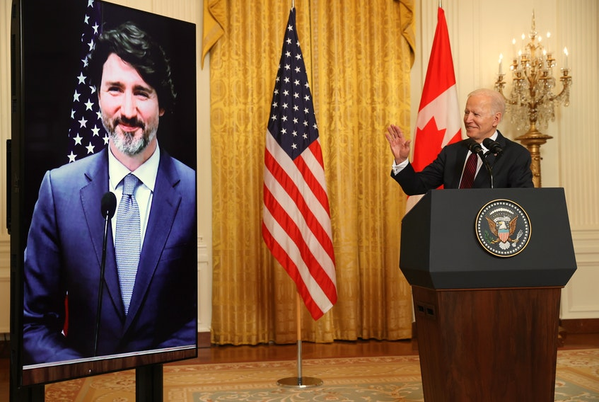 U.S. President Joe Biden gestures to Canada's Prime Minister Justin Trudeau, appearing via video conference call, during their virtual bilateral meeting on Feb. 23, 2021. REUTERS