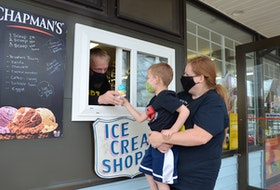 Four-year-old James Kroezen gets a lift from his mom, Heather Kroezen, as his dad, Bert Kroezen, hands him a cone of cookie monster through the new ice cream window at the Northend Market in Kentville. KIRK STARRATT