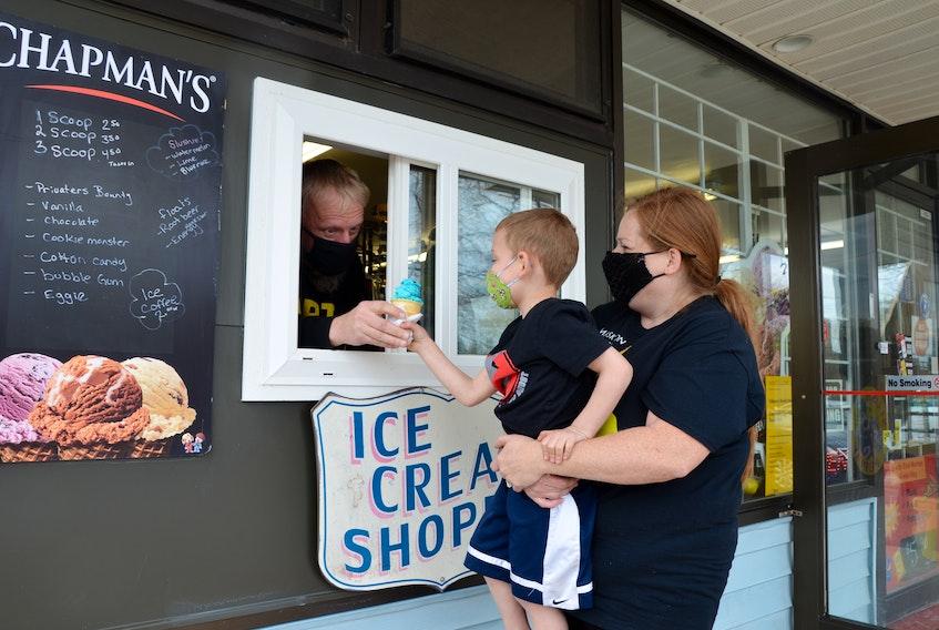 Four-year-old James Kroezen gets a lift from his mom, Heather Kroezen, as his dad, Bert Kroezen, hands him a cone of cookie monster through the new ice cream window at the Northend Market in Kentville. KIRK STARRATT