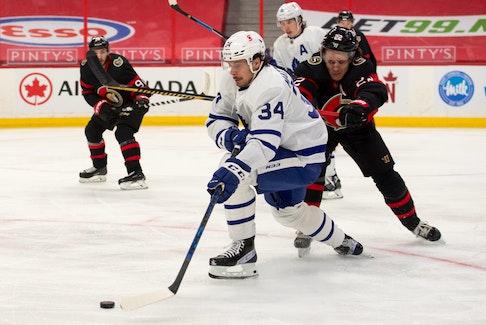 Toronto Maple Leafs centre Auston Matthews moves the puck past Ottawa Senators defenceman Nikita Zaitsev Wednesday in Ottawa as the regular season winds down.