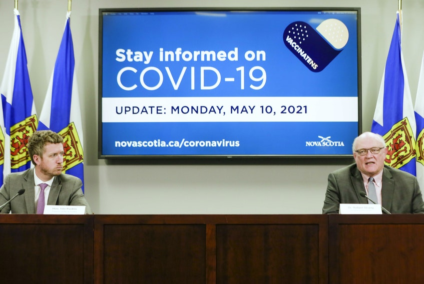 Premier Iain Rankin listens as Dr. Robert Strang, Nova Scotia's chief medical officer of health, speaks at a COVID-10 briefing in Halifax on Monday, May 10, 2021.