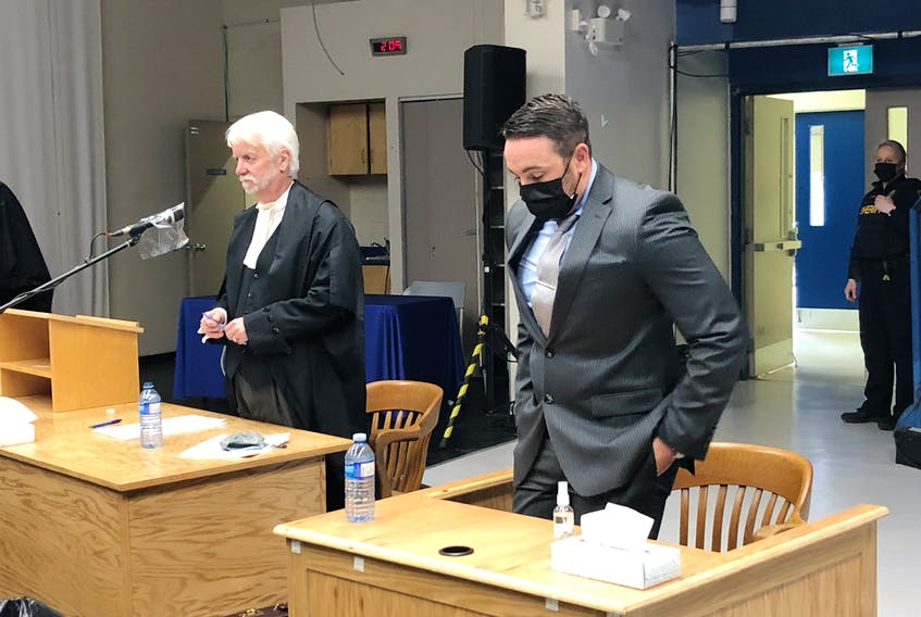 Royal Newfoundland Constabulary officer Doug Snelgrove (right) enters a St. John's courtroom Friday afternoon, upon learning the jury currently deliberating on a verdict in his sexual assault trial was returning with a series of questions for the judge. Snelgrove's trial is taking place in a temporary courtroom set up at the former School for the Deaf in St. John's, which offers more space than the courthouse for social distancing amid the COVID-19 pandemic.