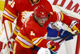 Flames defenceman Rasmus Andersson gives Vancouver Canucks winger Jayce Hawryluk a rough ride in front of the Flames net last night at the Saddledome.