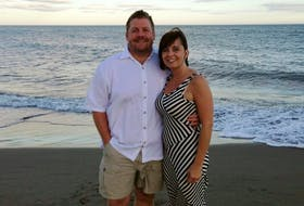 Paul MacKinnon property manager for Emerald Isle Property Management, and his wife Stacey Wyand posing for a photo on the beach.