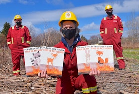 Elizabeth MacDonald, front, a member of the North Sydney Fire Department accompanied by some of their other firefighters Woody Woodfine, left, and Sean O'Connell, holds signs, part of the department's passionate new project in hopes of curbing grass fires and protecting wildlife. Sharon Montgomery-Dupe/Cape Breton Post