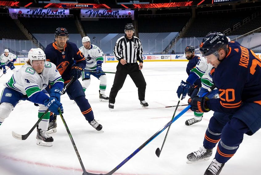 Slater Koekkoek (20) of the Edmonton Oilers battles for the puck against Brock Boeser (6) of the Vancouver Canucks at Rogers Place on May 15, 2021 in Edmonton.