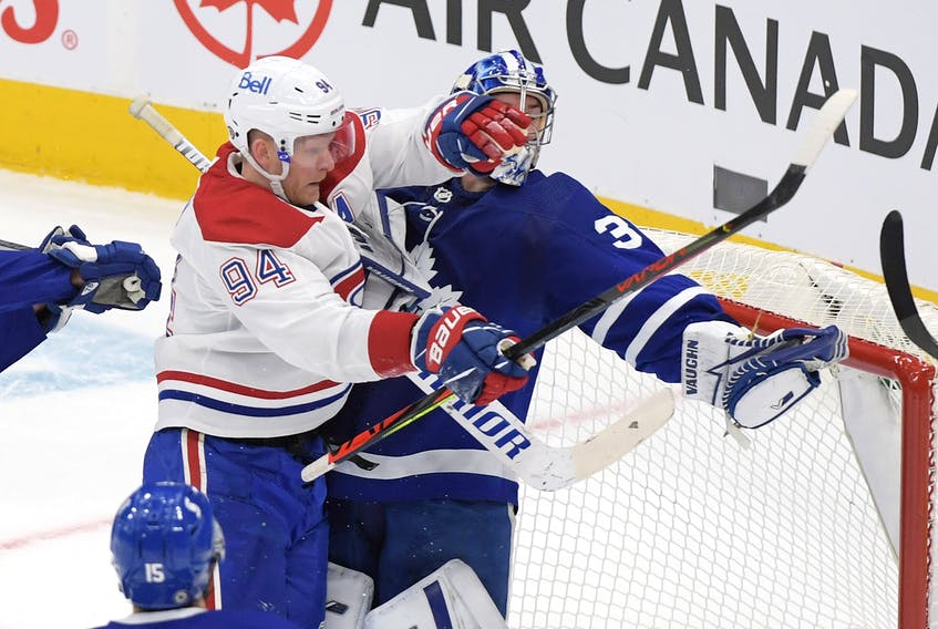 Toronto Maple Leafs goalie Jack Campbell (36) holds the puck in his glove as he is bodychecked by Montreal Canadiens forward Corey Perry earlier this season.