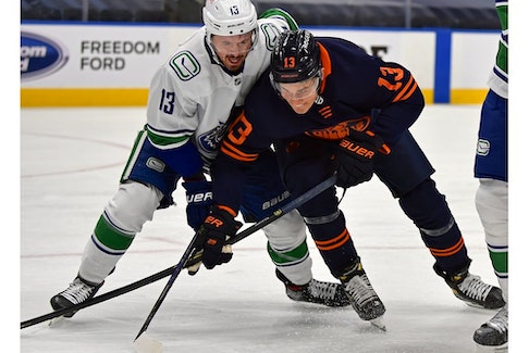 Edmonton Oilers Jesse Puljujarvi (13) and Vancouver Canucks Jayce Hawryluk (13) battle for the puck during NHL action at Rogers Place in Edmonton, May 15, 2021.