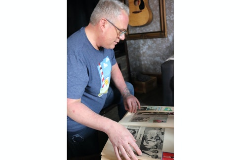 Jeffrey Haight looks through a scrapbook containing instances of gay representation he found in newspapers.