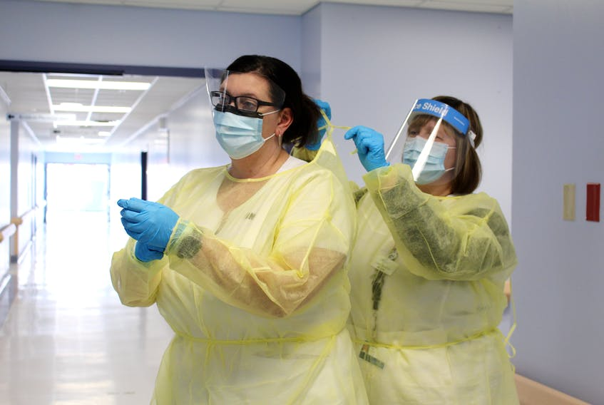 At Cape Breton Regional Hospital in Sydney, infection prevention and control practitioners Karrie Dunn, RN, left, and Lynn Boutilier, RN, demonstrate the types of personal protective equipment worn by staff and physicians who provide care to patients with COVID-19 which includes gowns, gloves, masks and face shields. Half the number of patients treated in the Cape Breton Regional Hospital COVID unit overall since the beginning of the pandemic, was over the past two weeks. Lynn Gilbert/Nova Scotia Health