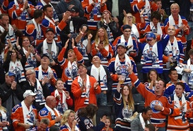 Fans celebrate a goal by Edmonton Oilers star Connor McDavid against the Calgary Flames during the season opener of NHL action at Rogers Place in Edmonton on Oct. 4, 2017.