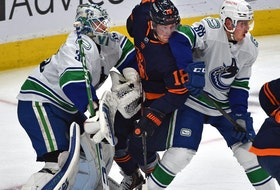 Edmonton Oilers James Neal (18) gets sandwich between Vancouver Canucks Nate Schmidt (88) and goalie Thatcher Demko (35) during NHL action at Rogers Place in Edmonton, May 6, 2021.