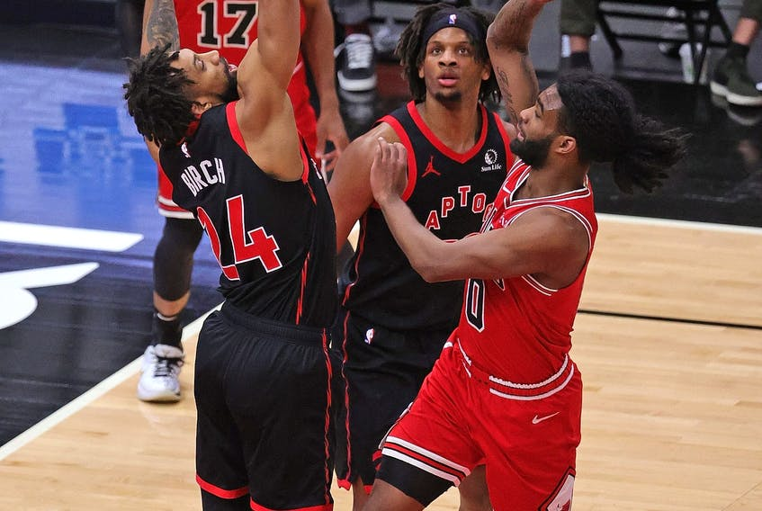 Coby White #0 of the Chicago Bulls shoots over Khem Birch #24 and Freddie Gillespie #55 of the Toronto Raptors at the United Center on May 13, 2021 in Chicago. The Bulls defeated the Raptors 114-102.