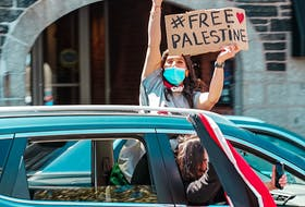 A protester peaks out of a car's sunroof during the #FreePalestine rally in Halifax Saturday, May 15, 2021. Photo Credit: Mohammed Al-Karmanji