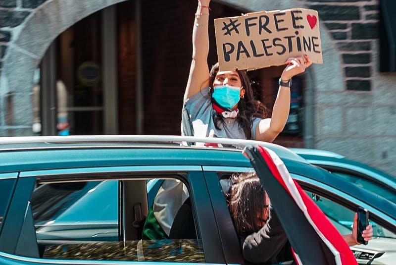 A protester peaks out of a car's sunroof during the #FreePalestine rally in Halifax Saturday, May 15, 2021. Photo Credit: Mohammed Al-Karmanji - Contributed