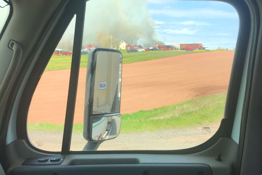 A motorist travelling on Route 2 in Springvale took this picture of firefighters in the distance battling a blaze that destroyed two buildings on Monday afternoon.