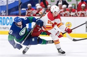 Calgary Flames' Dillon Dube (29) checks Vancouver Canucks' Matthew Highmore (15) during the first period.