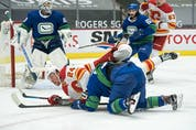 Vancouver Canucks defenceman Olli Juolevi (48) checks Calgary Flames forward Brett Ritchie (24) in the second period at Rogers Arena.