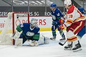 Calgary Flames forward Matthew Tkachuk (19) scores on Vancouver Canucks goalie Braden Holtby (49) in the second period at Rogers Arena.
