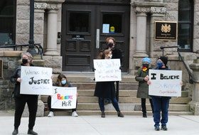 "Activist and survivor Heather Elliott (centre) participates in a show of support outside the Newfoundland and Labrador Supreme Court building in St. John's Saturday for the woman known to the public as Jane Doe — the survivor of a sexual assault by Royal Newfoundland Constabulary officer Doug Snelgrove in 2014. ""We See You. We Support You. #SupportForJaneDoe,"" Elliott's sign reads."
