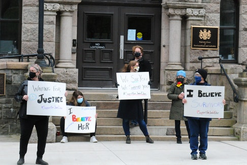 """Activist and survivor Heather Elliott (centre) participates in a show of support outside the Newfoundland and Labrador Supreme Court building in St. John's Saturday for the woman known to the public as Jane Doe — the survivor of a sexual assault by Royal Newfoundland Constabulary officer Doug Snelgrove in 2014. """"We See You. We Support You. #SupportForJaneDoe,"""" Elliott's sign reads."""