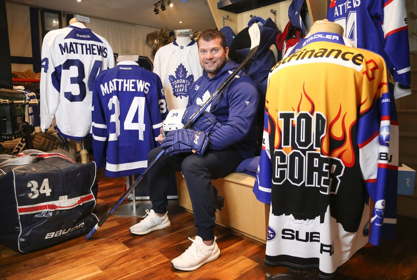 Mark Fera sits with some of the items from his extensive Auston Matthews collection that includes jerseys, gloves, pucks and helmets.