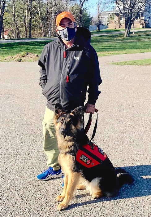 Len Harris, who suffered serious injuries that often make it difficult to walk, has taught his German shepherd Karma to carry a cane and lie on the ground whenever he limps badly. Chris Connors/Cape Breton Post - Christopher Connors